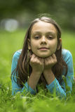 portrait of cute little girl lying on green grass. Stock Photography
