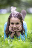 Portrait of cute little girl lying in green grass. Happy. Stock Photo