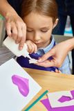Adorable Little Girl in Craft Class. Portrait of cute little girl making handmade gift card with heart shape during art and craft class in pre-school, with stock images