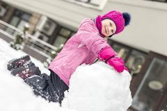 Portrait of cute little girl making smowman. at bright winter day. Adorable child playing with snow outdoors. Funny Stock Photo