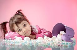Portrait of a cute little girl with marshmallow on pink backgrou Stock Photography