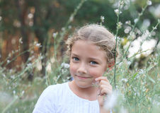 Portrait of a cute little girl on the nature in flowers. Royalty Free Stock Photo