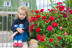 Portrait of cute little girl near the flowers in Royalty Free Stock Images