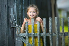 Portrait of cute little girl near the wooden fence Royalty Free Stock Photography