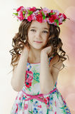 Portrait of cute little girl in nice spring dress, with flower wreath on head, showing emotions. Portrait of cute little girl in nice spring dress, with flower stock images