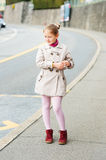 Portrait of a cute little girl. Outdoor portrait of a cute little girl, wearing beige coat and red shoes Royalty Free Stock Photography