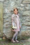 Portrait of a cute little girl. Outdoor portrait of a cute little girl with white roses, wearing beige coat and pink dress Royalty Free Stock Photo