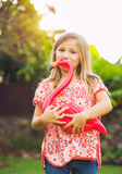 Portrait of cute little girl outside with pink flamingo Royalty Free Stock Image