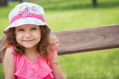 Portrait of cute little girl in a park Stock Photos