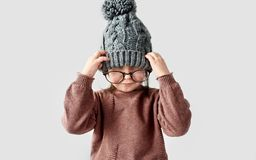 Portrait of cute little girl playing in the winter warm hat, wearing sweater with round stylish spectacles on a white studio royalty free stock photos