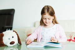 Portrait of a cute little girl. Reading a book indoors Stock Image
