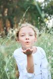 Portrait of a cute little girl sends an air kiss on the nature. Royalty Free Stock Images