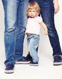 Portrait of a cute little girl in shirt and jeans standing with her parents on white background. Royalty Free Stock Image