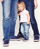 Portrait of a cute little girl in shirt and jeans standing with her parents on white background. Stock Photo