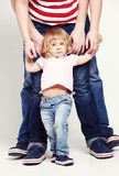 Portrait of a cute little girl in shirt and jeans standing with her parents on white background. royalty free stock photo