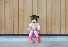 Portrait of cute little girl sit and hugging Teddy Bear against wood plank wall royalty free stock photos