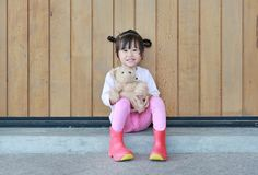 Portrait of cute little girl sit and hugging Teddy Bear against wood plank wall stock photo