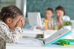 Portrait of cute little girl sitting in classroom stock photos