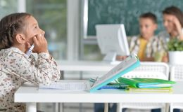 Portrait of cute little girl sitting in classroom stock photo
