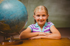 Portrait of cute little girl sitting at desk Stock Image