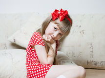 Portrait of a cute little girl sitting on the floor Royalty Free Stock Photos