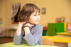 Portrait of cute little girl sitting with hands clasped at desk in classroom royalty free stock photography
