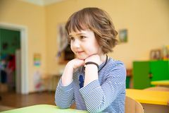 Portrait of cute little girl sitting with hands clasped at desk in classroom stock images