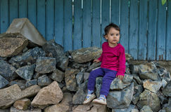 Portrait of cute little girl sitting on rocks at countryside Royalty Free Stock Photo