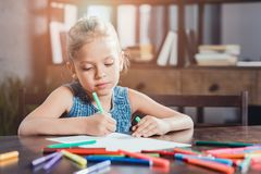 Portrait of cute little girl sitting at table and drawing picture. At home royalty free stock images