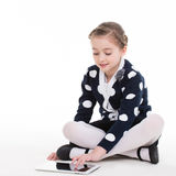 Portrait of cute little girl sitting with the tablet. Stock Image