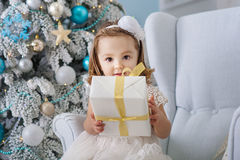 Portrait of cute little girl smiling and holding boxes with gifts near the Christmas tree. New Year. Holiday fun. Happy royalty free stock photography
