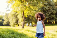 Portrait of little girl standing and looking confused stock images