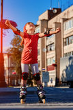 Portrait of the cute little girl standing in roller skates in the city-park in warm sunshiny day. Beautiful girl dressed in the colorful sportwear with knee Royalty Free Stock Photos