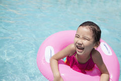 Portrait of a cute little girl swimming in the pool with a pink tube Stock Images