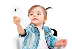 Portrait of cute little girl, taking selfie on mobile phone stock photography