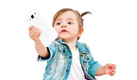 Portrait of cute little girl taking selfie on mobile phone. Isolated on white background royalty free stock image