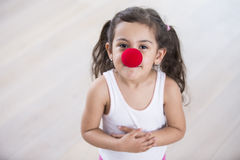 Portrait of cute little girl wearing clown nose at home Royalty Free Stock Photos