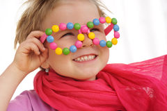 Portrait of cute little girl wearing funny glasses, decorated with colorful smarties, candies. Portrait of cute little girl wearing funny glasses, decorated with Stock Photo