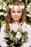 Portrait of cute little girl on white dress and wreath on first holy communion background church gate. Portrait of cute little girl on white dress and wreath on royalty free stock images