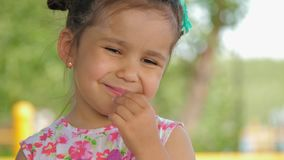 Portrait of a cute little girl who eats black currant. stock footage