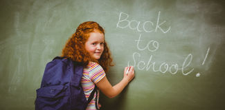 Portrait of cute little girl writing on blackboard. In the classroom Stock Image