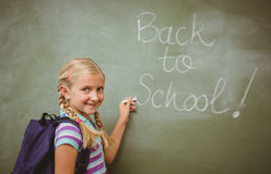 Portrait of cute little girl writing on blackboard. In the classroom Stock Photography