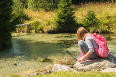 Portrait of a cute little girl. Cute little girl of 7-8 years old hiking in swiss Alps, resting by the river, wearing sport clothes, trainers and backpack, back stock photo