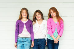 Portrait of cute little girls. Group of 3 little girls standing outdoors against white wooden background, wearing denim jeans and colorful jackets royalty free stock images