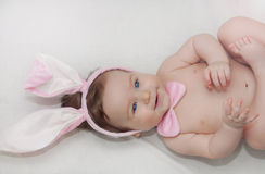 Portrait of cute little happy baby boy with rabbit's ears lying Royalty Free Stock Images