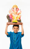 Portrait of cute little Indian boy holding a Ganesh idol or lord ganesha or ganapati murti /statue over his head, taking home on G stock photos