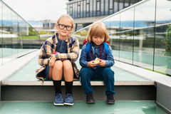 Portrait of a cute little kids. Cute kids with backpacks sitting on stairs next to school, wearing backpack, eating apples Stock Images