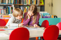 Portrait of cute little kids. Two adorable kids, little girl and her brothe reading book in a library Royalty Free Stock Photo