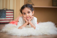 Portrait of cute little latino girl. Lying on wite carpet Royalty Free Stock Photography