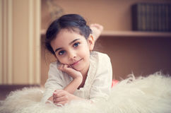 Portrait of cute little latino girl. Lying on wite carpet Royalty Free Stock Image